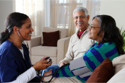 The caregiver checks the blood pressure of the old woman